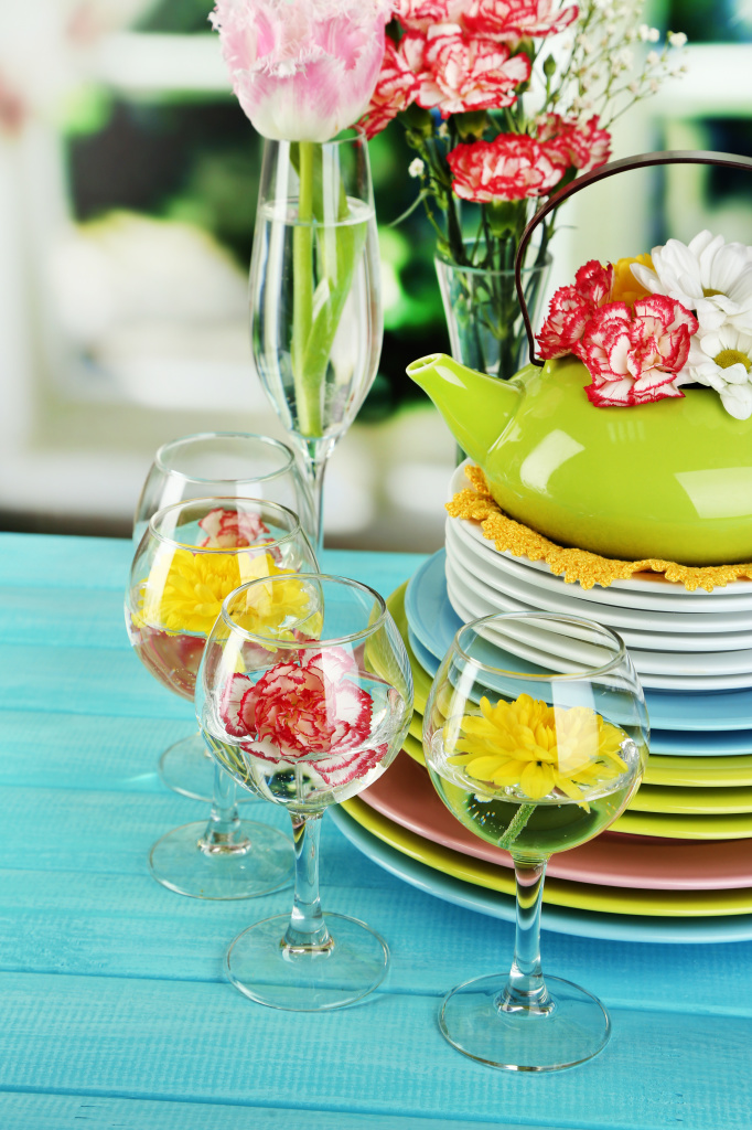 Stack of colorful ceramic dishes and flowers,